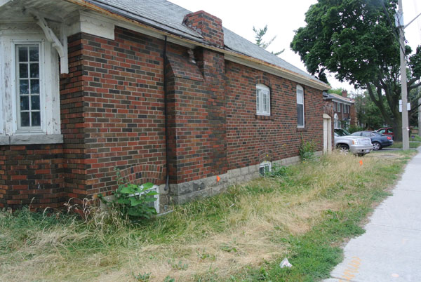 A sad case of neglect – a property standards issue (rusted eavestrough, peeling, flaking paint, chimney with a few bricks short of a load, turf grass left to overgrow and weeds appearing).