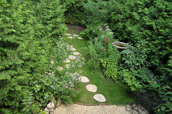 In the backyard - hard edges meet soft. Gold pebble aggregate provides a loose patio substrate, reclaimed bricks from the demolition next door hold the stones, and Eco-lawn lines the pathway embedded with concrete, dendro-stepping stones.